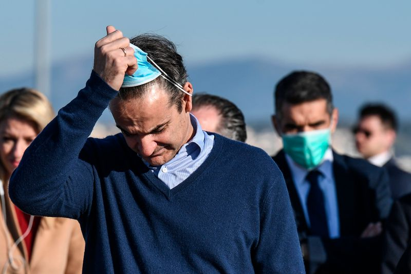 Greek Prime Minister Kyriakos Mitsotakis removes his face mask after attending the departure of unaccompanied minors who were living in migrant camps on the Greek islands to travel on a special flight to Germany at Athens International Airport on April 18.