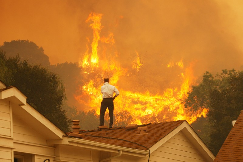 A man on a rooftop looks at approaching flames as a wildfire continues to grow near Camarillo, California, on May 3, 2013.