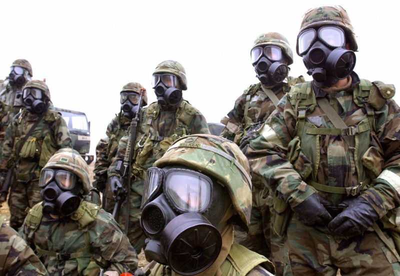 U.S. soldiers wearing gas masks wait for orders during a chemical warfare exercise in Yeoncheon near the North Korea-South Korea border on Feb. 26, 2003.