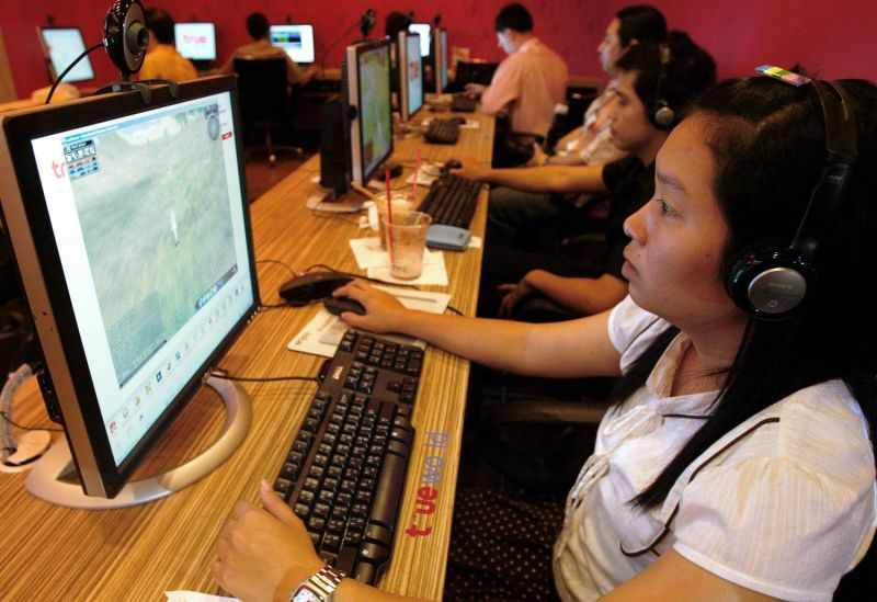 Thai locals download music at an internet cafe in downtown Bangkok on Feb. 3, 2006.