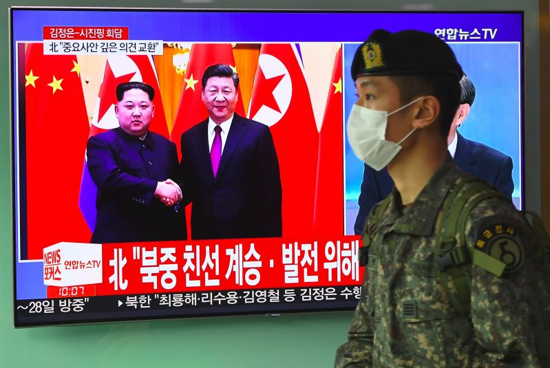 In Seoul, a South Korean soldier walks past a television screen showing North Korean leader Kim Jong Un with Chinese President Xi Jinping in China, on March 28, 2018.