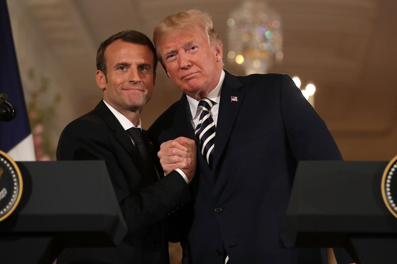 French President Emmanuel Macron (left) and U.S. President Donald Trump embrace at the completion of a joint press conference in the East Room of the White House in Washington on April 24, 2018.