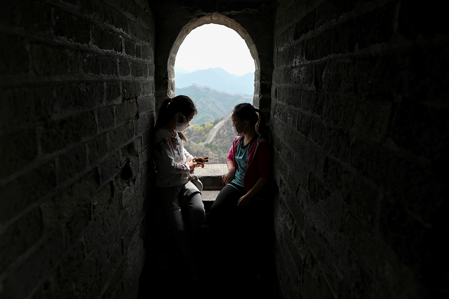 Two children rest during their visit to the Great Wall of China in Beijing on April 18. WANG ZHAO/AFP via Getty Images