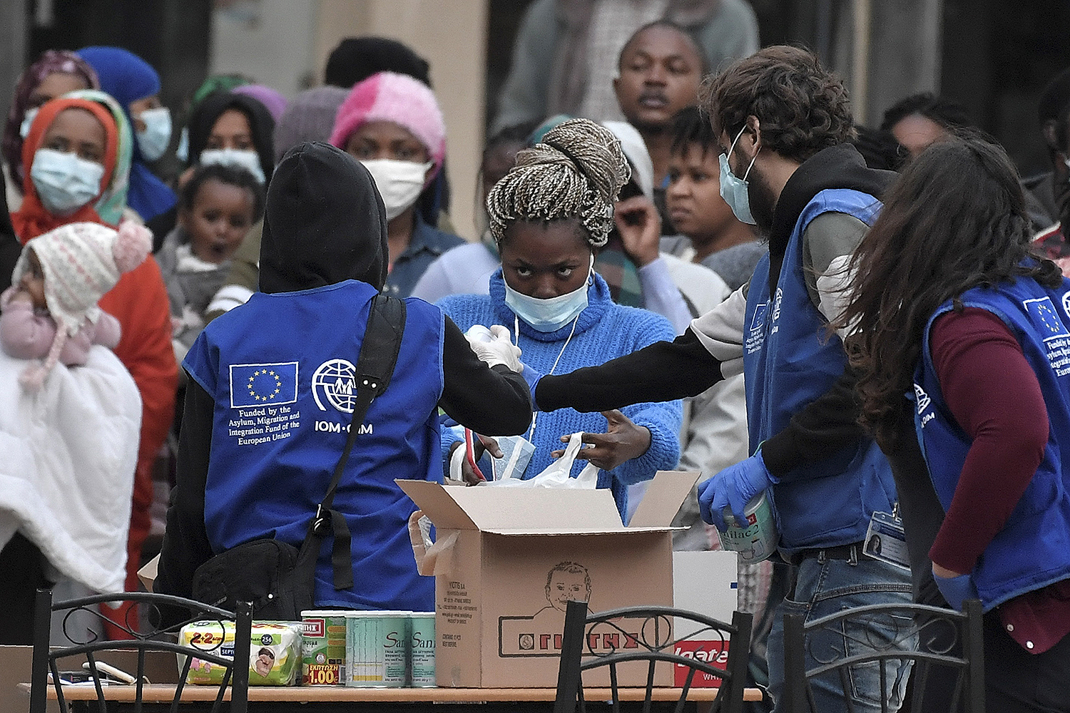 Migrants stand in line to get sanitizer and other items during a distribution by the International Organization for Migration near Kranidi, Greece, on April 21. LOUISA GOULIAMAKI/AFP via Getty Images