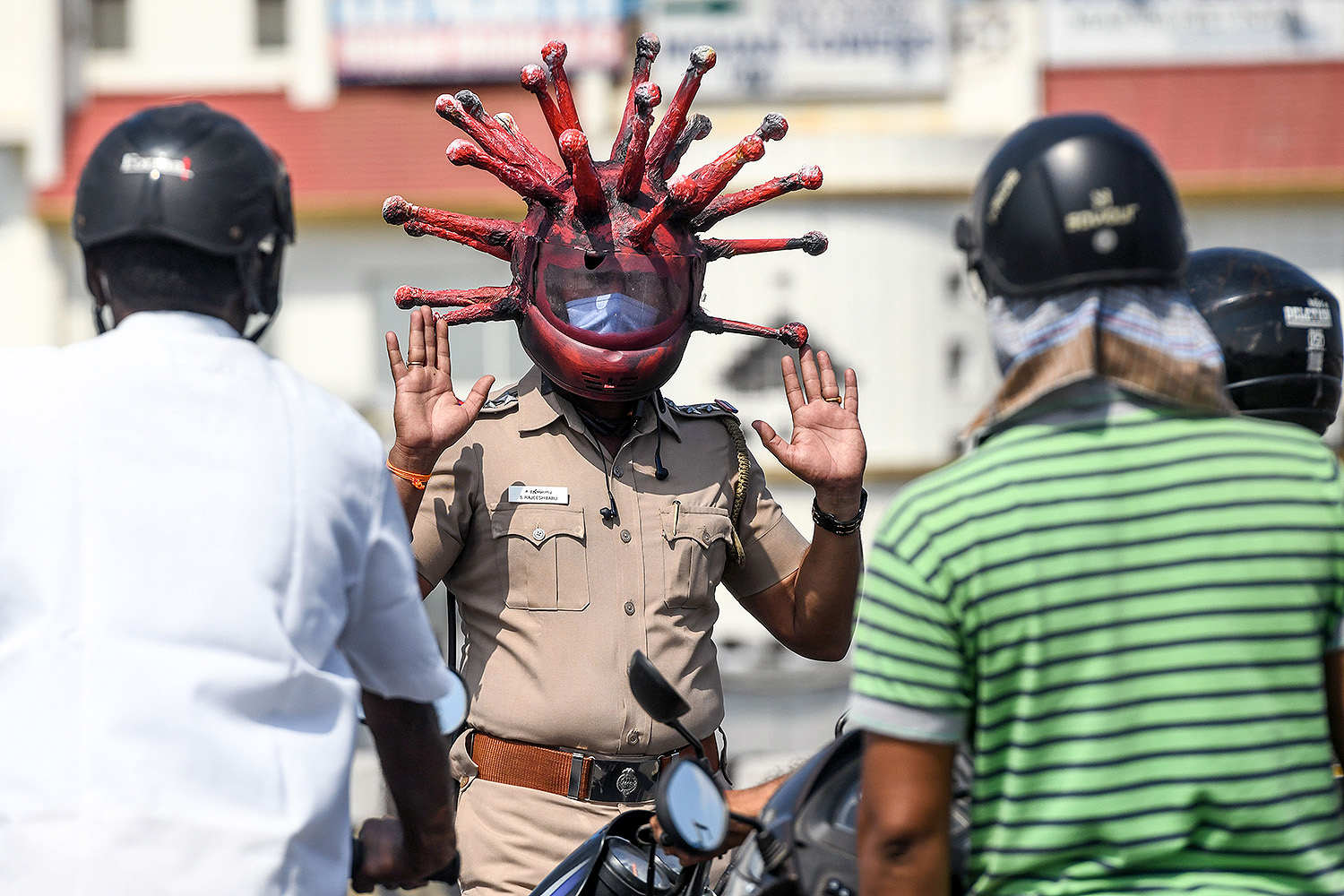Wearing a coronavirus-themed helmet, police inspector Rajesh Babu speaks to motorists at a checkpoint during a government-imposed lockdown in Chennai, India, on March 28. ARUN SANKAR/AFP via Getty Images