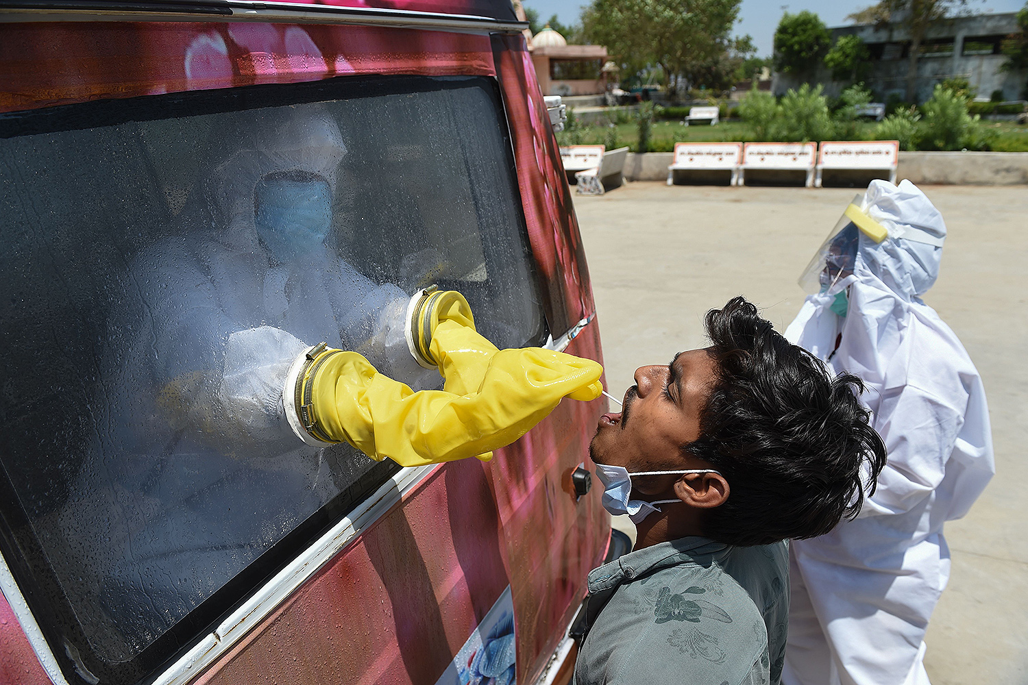 From inside a mobile testing van, a health official collects a sample to test for COVID-19 near Ahmedabad, India, on April 23. SAM PANTHAKY/AFP via Getty Images