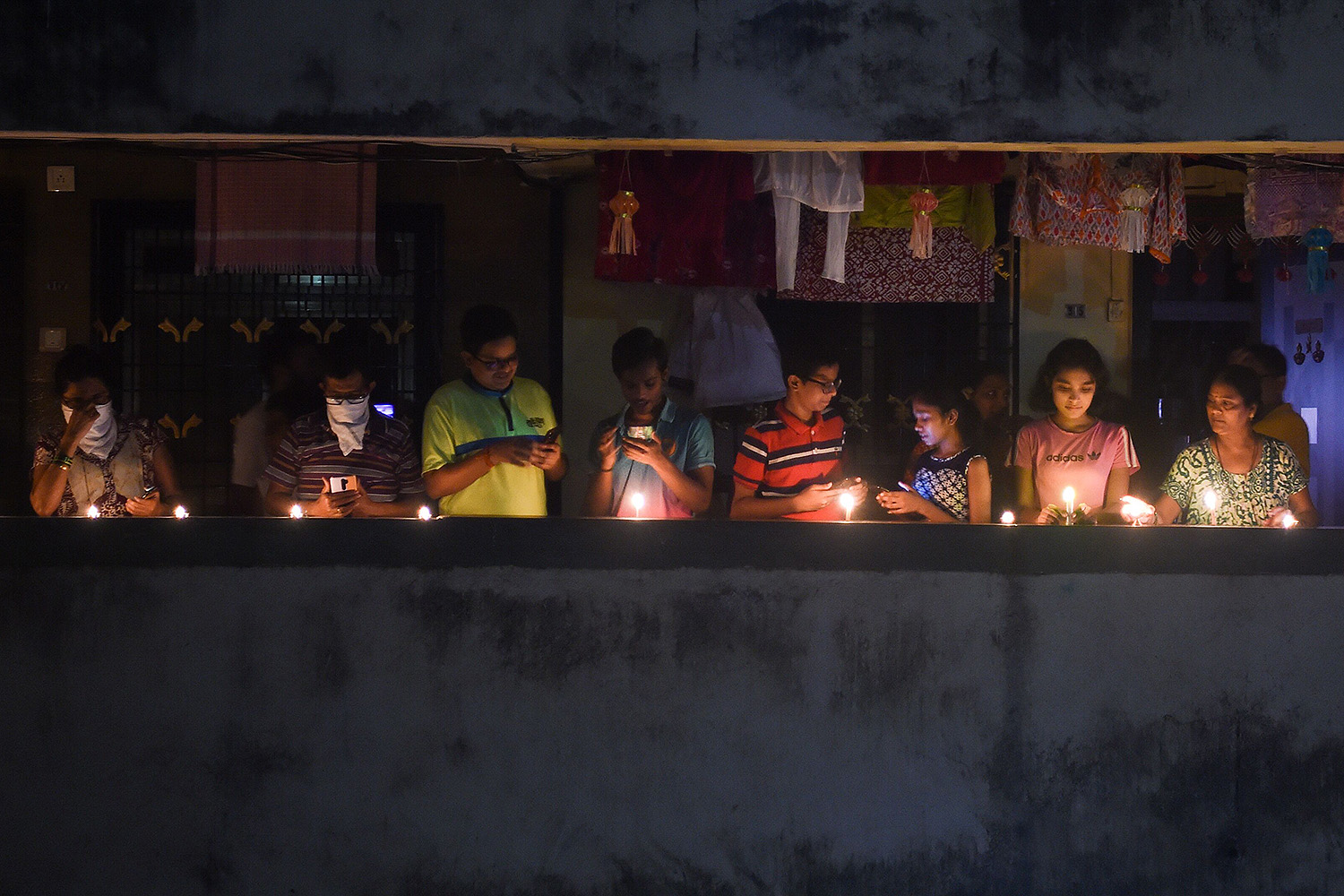 From their balconies, residents in Mumbai light candles and turn on their cellphone lights during a nine-minute vigil called by India's prime minister April 5 to show unity and solidarity in the fight against the coronavirus. PUNIT PARANJPE/AFP via Getty Images