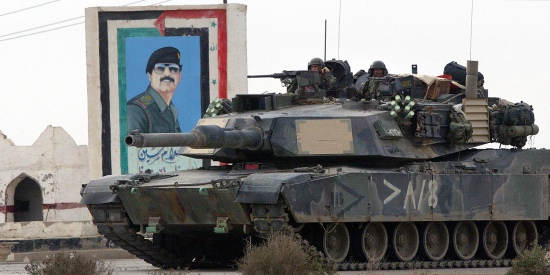 Days after the United States invaded Iraq, a tank from the U.S. Marine Task Force Tarawa sets up position in front of a painting of Saddam Hussein in the southern Iraqi city of Nasiriyah on March 24, 2003.