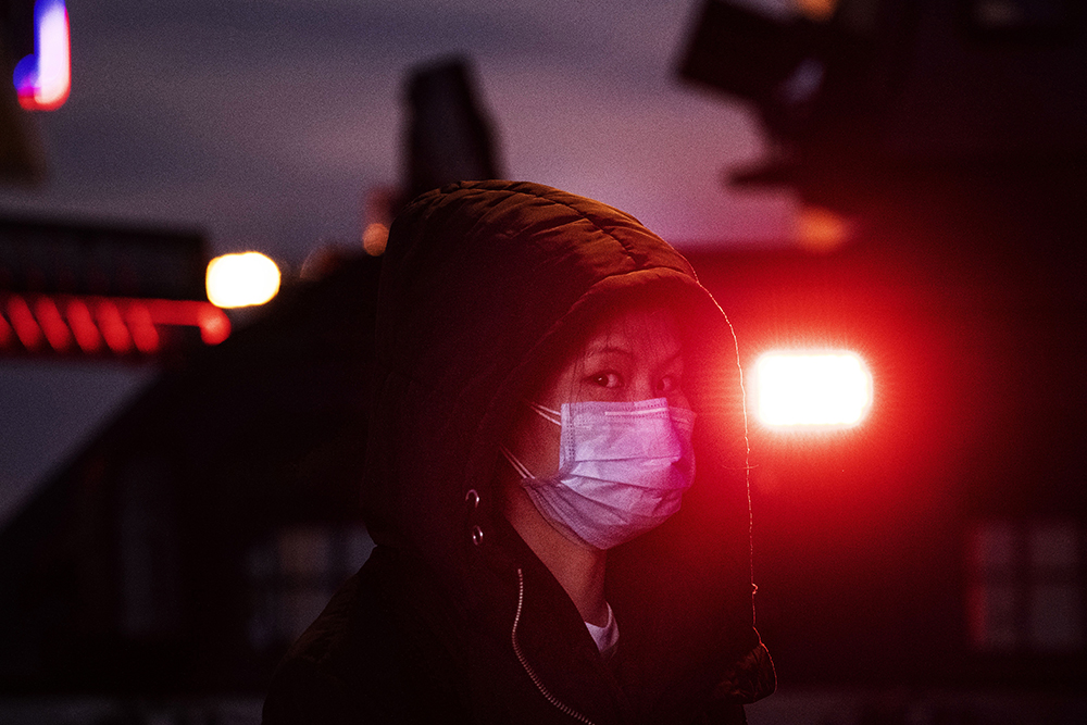 BEIJING, CHINA - JANUARY 21: A Chinese woman wears a mask as she stands near the light of a police vehicle on regular duty at Beijing Railway station before the annual Spring Festival on January 21, 2020 in Beijing, China. The number of cases of a deadly new coronavirus rose to nearly 300 in mainland China Tuesday as health officials stepped up efforts to contain the spread of the pneumonia-like disease which medicals experts confirmed can be passed from human to human. The number of those who have died from the virus in China climbed to six on Tuesday and cases have been reported in other parts of Asia including in Thailand, Japan, Taiwan and South Korea. (Photo by Kevin Frayer/Getty Images)