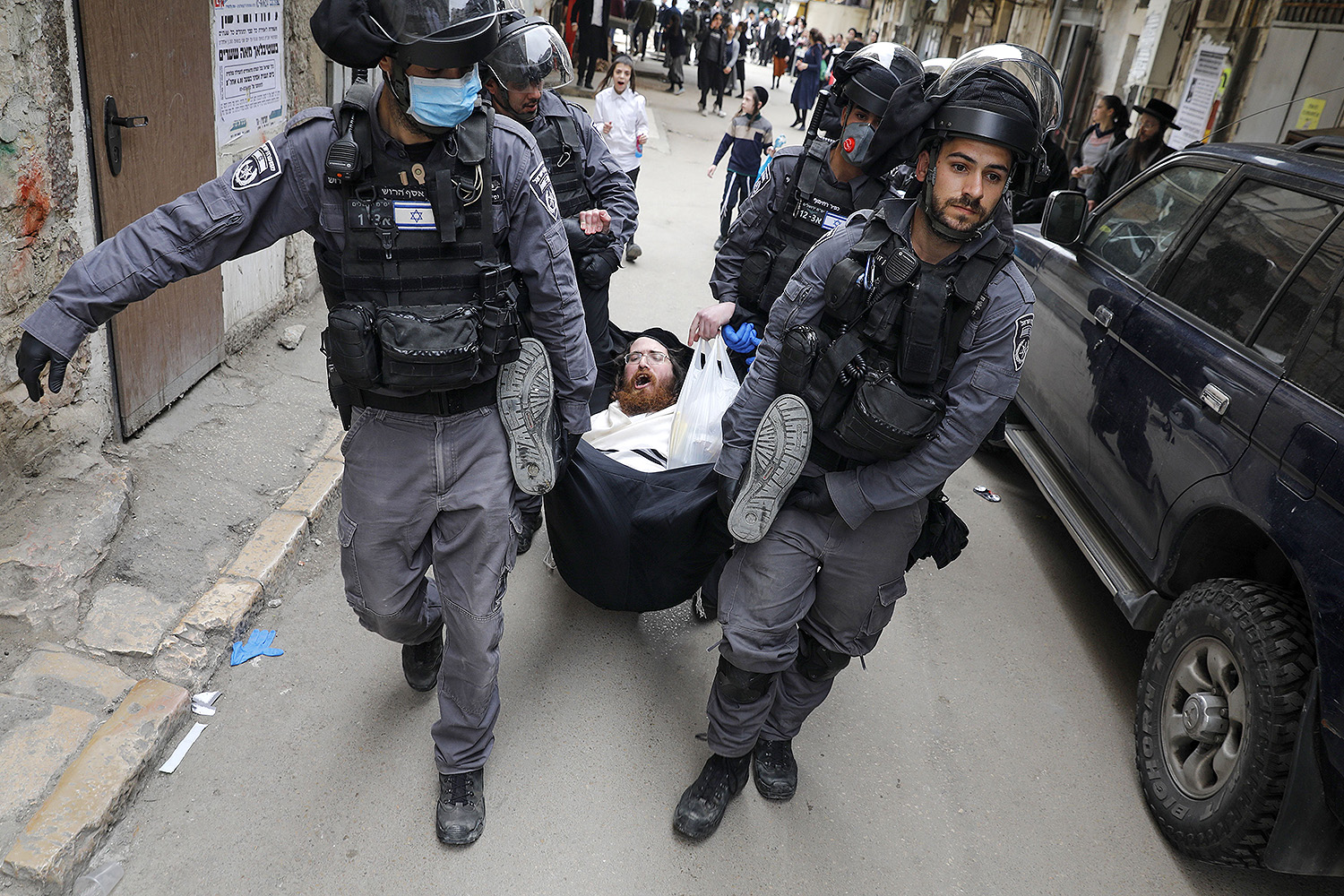 Israeli security forces arrest an ultra-Orthodox Jewish man as they close a synagogue in the Mea Shearim neighborhood in Jerusalem on March 30 amid efforts to curb the spread of the coronavirus. AHMAD GHARABLI/AFP via Getty Images