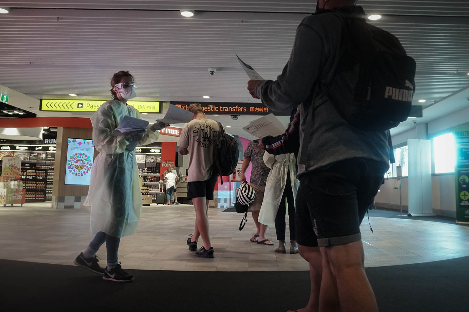 "A volunteer hands out ""isolation guidance"" to passengers arriving at Brisbane International Airport in Australia on March 20."