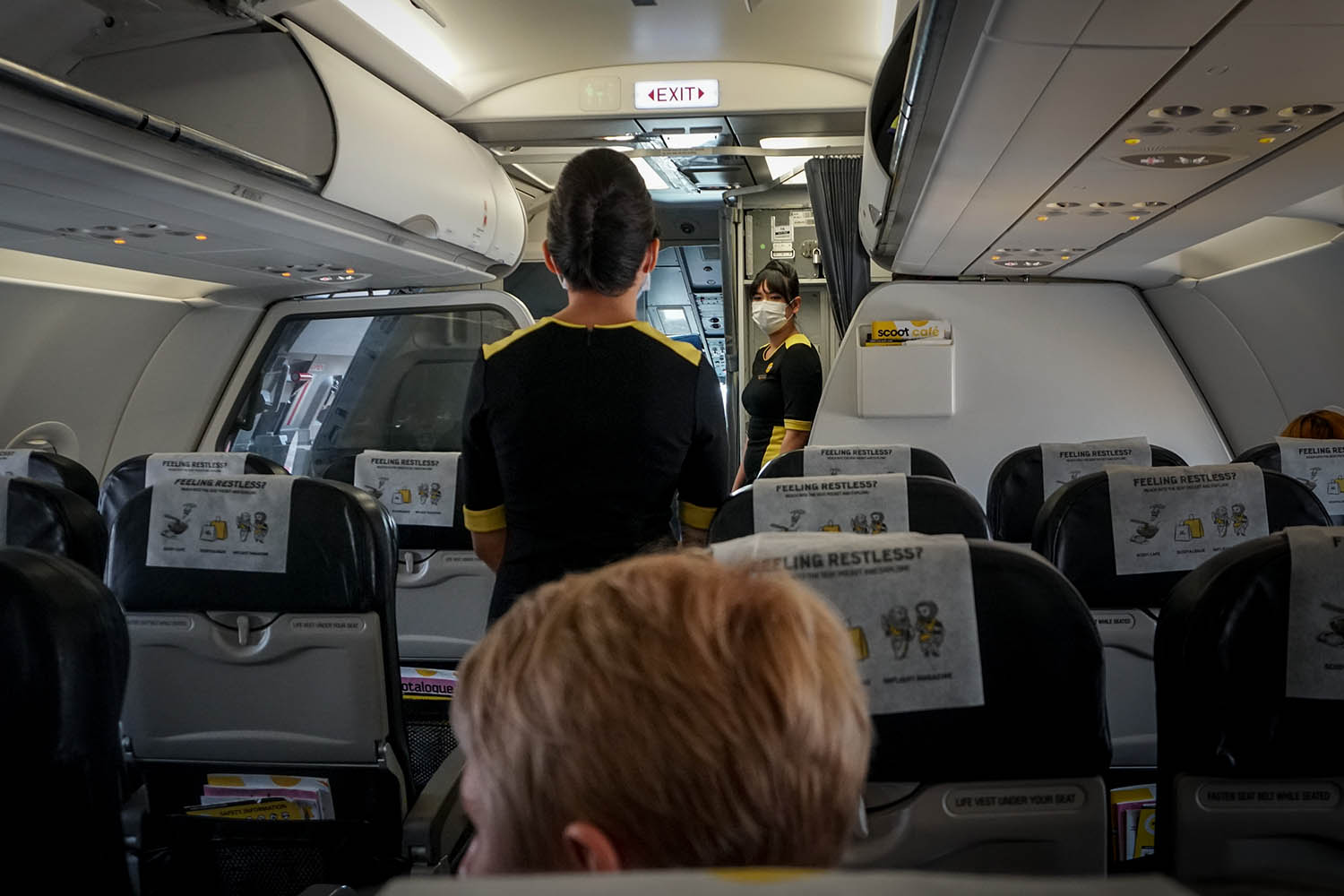 Crew members wear facemasks to prevent the spread of the coronavirus on one of the few remaining flights from Laos to Singapore on March 19. Passengers hoped to return to New Zealand, the United Kingdom, and Australia from there.