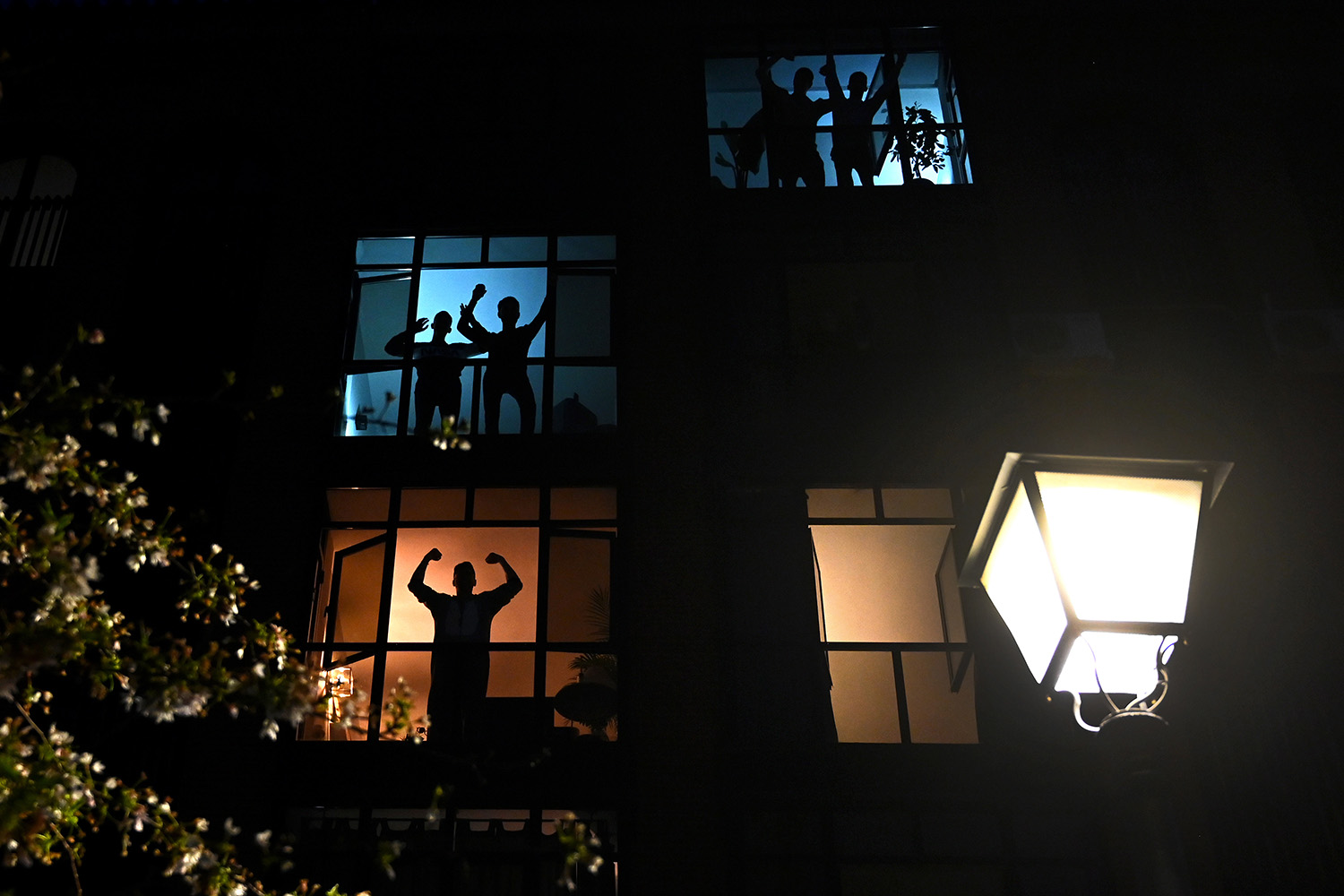 During a nationwide lockdown, neighbors in Madrid applaud from their windows in tribute to the health care workers dealing with the COVID-19 pandemic March 28. GABRIEL BOUYS/AFP via Getty Images