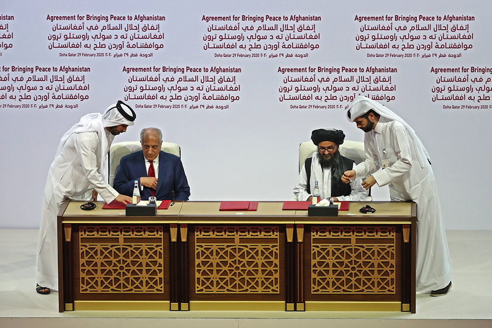 (L to R) US Special Representative for Afghanistan Reconciliation Zalmay Khalilzad and Taliban co-founder Mullah Abdul Ghani Baradar sign the US-Taliban peace agreement during a ceremony in the Qatari capital Doha on February 29, 2020. - The United States signed a landmark deal with the Taliban, laying out a timetable for a full troop withdrawal from Afghanistan within 14 months as it seeks an exit from its longest-ever war. (Photo by KARIM JAAFAR / AFP) (Photo by KARIM JAAFAR/AFP via Getty Images)