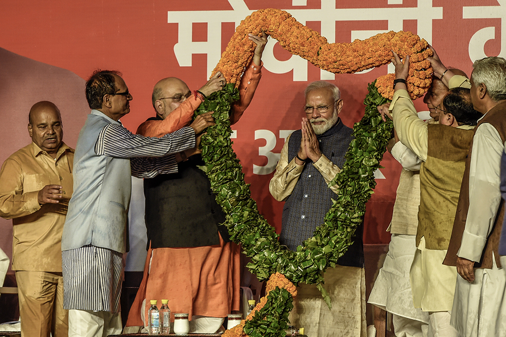 NEW DELHI, INDIA - MAY 23: Narendra Modi acknowledges to the victorious party workers while getting garland at the BJP party head quarters in New Delhi, India. Indian Prime Minister Narendra Modis Bharatiya Janata Party (BJP) is set for another five-year term on Thursday after a landslide victory as over 600 million people voted in a marathon seven-phase general elections which lasted over six-weeks. Supporters of the Hindu nationalist party celebrated in the capital New Delhi as Modi is scheduled to appear at the BJP headquarters and leaders across the world congratulated the Indian Prime Minister for his historic return to power for a second straight term. (Photo by Atul Loke/Getty Images)