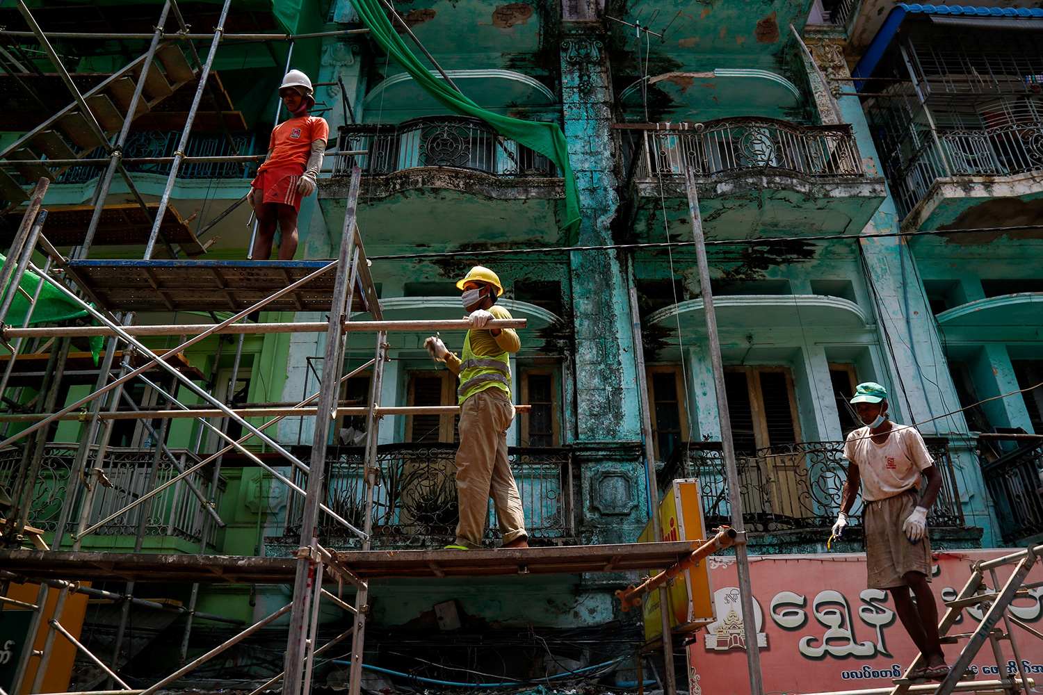 Construction workers stand on scaffolding in front of a building in Yangon, Myanmar, on April 21. SAI AUNG MAIN/AFP via Getty Images