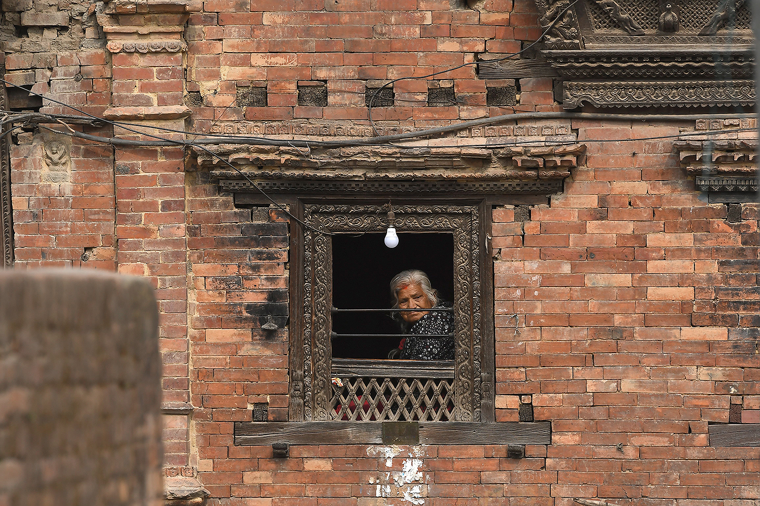 A woman looks outside her window during a nationwide lockdown in Bhaktapur, Nepal, on the outskirts of Kathmandu, on April 13. PRAKASH MATHEMA/AFP via Getty Images
