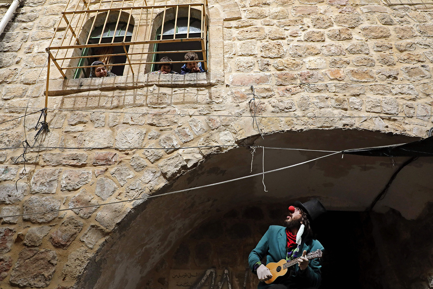 Artist Ameer Abu Ghalioon plays music dressed as a clown under the windows of Palestinian families on lockdown in the divided West Bank town of Hebron on March 31. HAZEM BADER/AFP via Getty Images