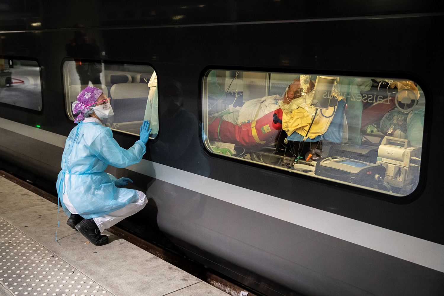 From a platform of the Gare d'Austerlitz train station in Paris on April 1, a medical worker looks through the window of a medicalized TGV high-speed train before its evacuation of coronavirus patients. The patients were being transferred from Paris's hospitals to those in the Brittany region of western France, where the outbreak has so far been limited. THOMAS SAMSON/POOL/AFP via Getty Images