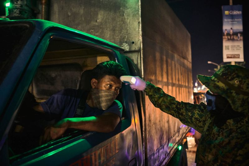 An officer takes the temperature of a commuter passing through a police checkpoint in Quezon City, the Philippines