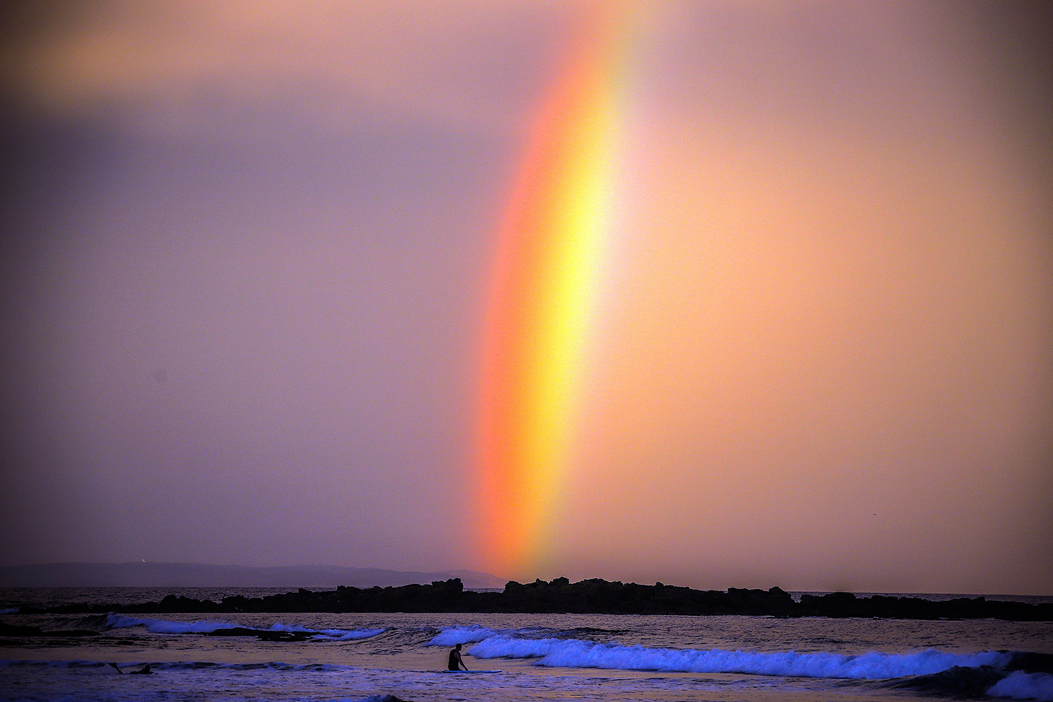 A rainbow appears behind a surfer at sunset on Narrawallee Beach in Mollymook, Australia, on April 10. DAVID GRAY/AFP via Getty Images