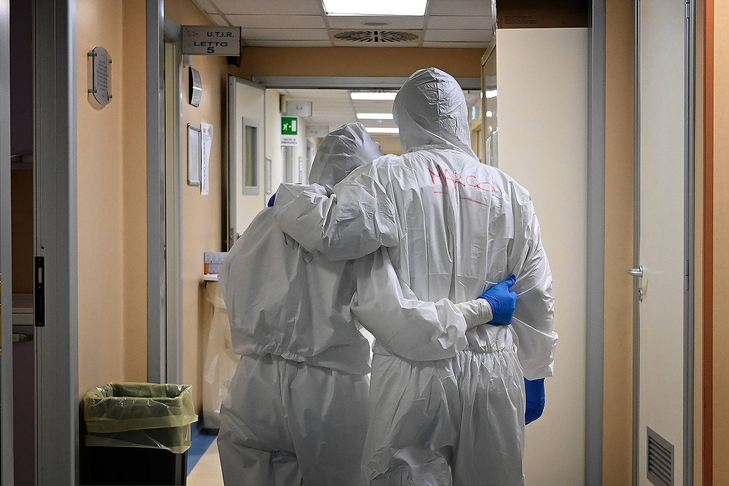 At the end of their shift treating COVID-19 patients, a doctor and nurse walk down a corridor in the intensive care unit of San Filippo Neri Hospital in Rome on April 20. ALBERTO PIZZOLI/AFP via Getty Images