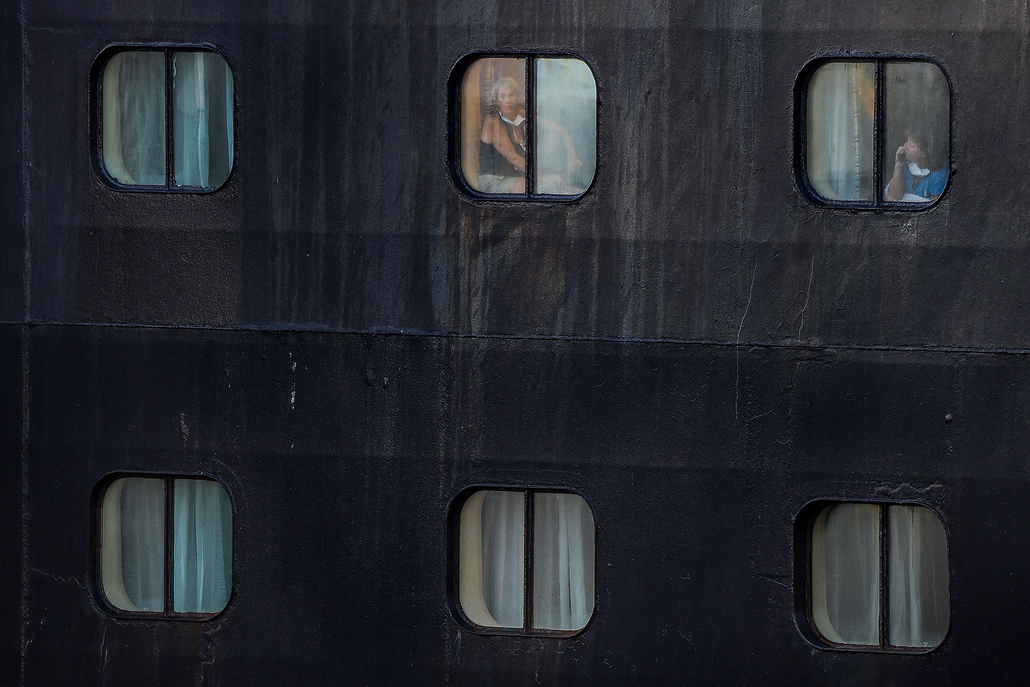 Passengers look out the window of Holland America's cruise ship Rotterdam as it docks at Port Everglades in Fort Lauderdale, Florida, on April 2. CHANDAN KHANNA/AFP via Getty Images