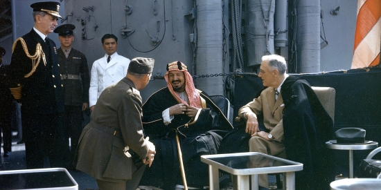 Saudi King Abdulaziz ibn Abdul Rahman Al Saud (center) and U.S. President Franklin Delano Roosevelt meet aboard the USS Quincy on Feb. 14, 1945. A military translator is pictured to the king's left.