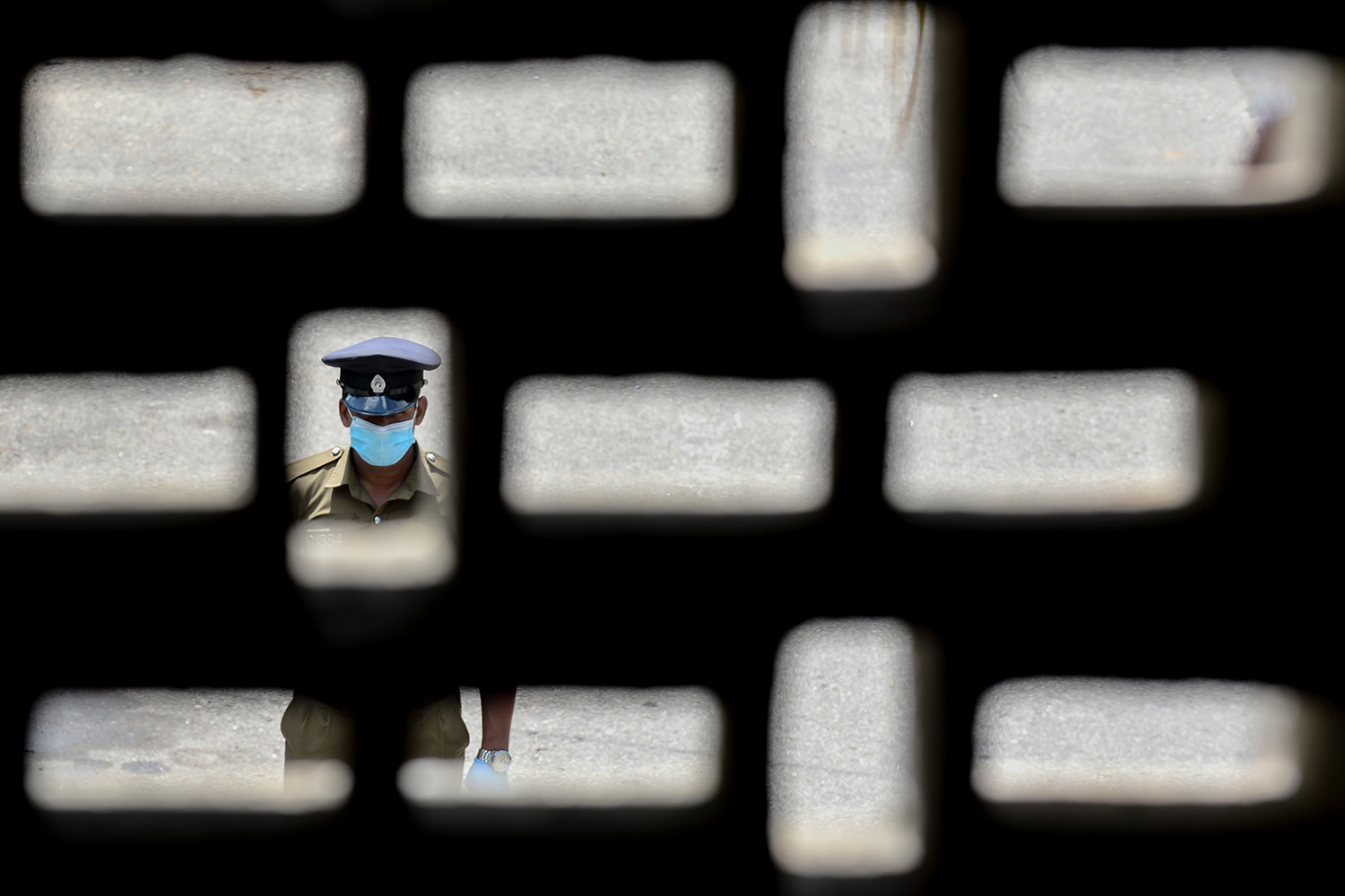 A policeman wearing a face mask stands guard outside a housing complex during a government-imposed nationwide lockdown in Colombo, Sri Lanka, on April 14. LAKRUWAN WANNIARACHCHI/AFP via Getty Images