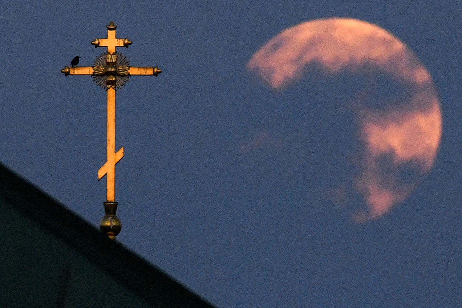 The supermoon shines from behind a church cross in downtown Moscow on April 8. KIRILL KUDRYAVTSEV/AFP via Getty Images