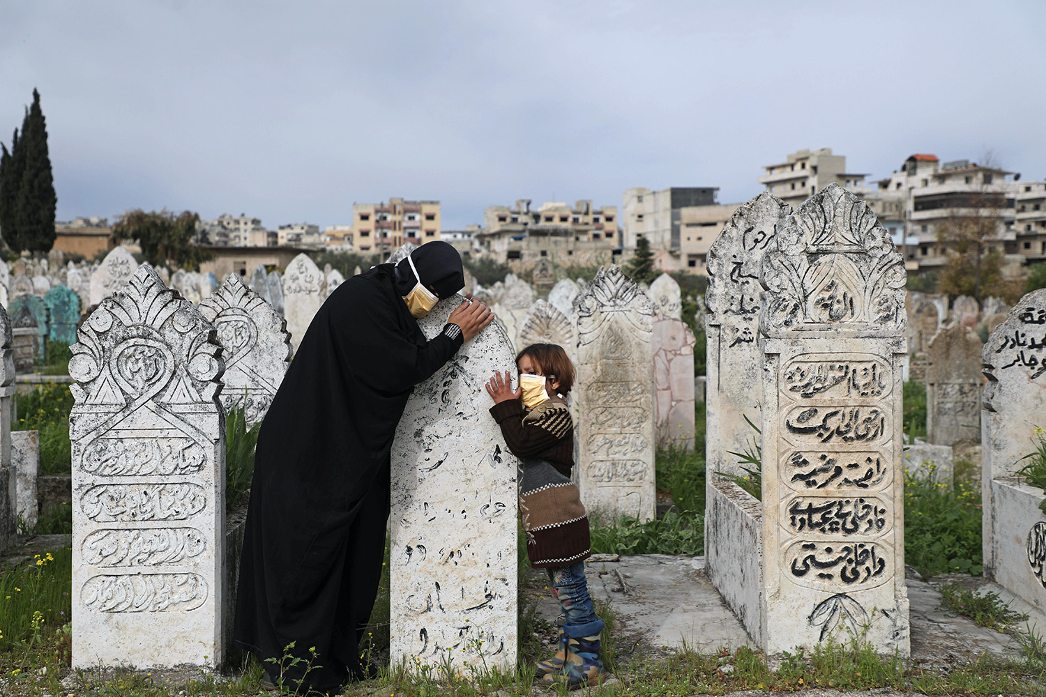A woman and her daughter visit the grave of a relative in Ariha, Syria, on April 5. AAREF WATAD/AFP via Getty Images