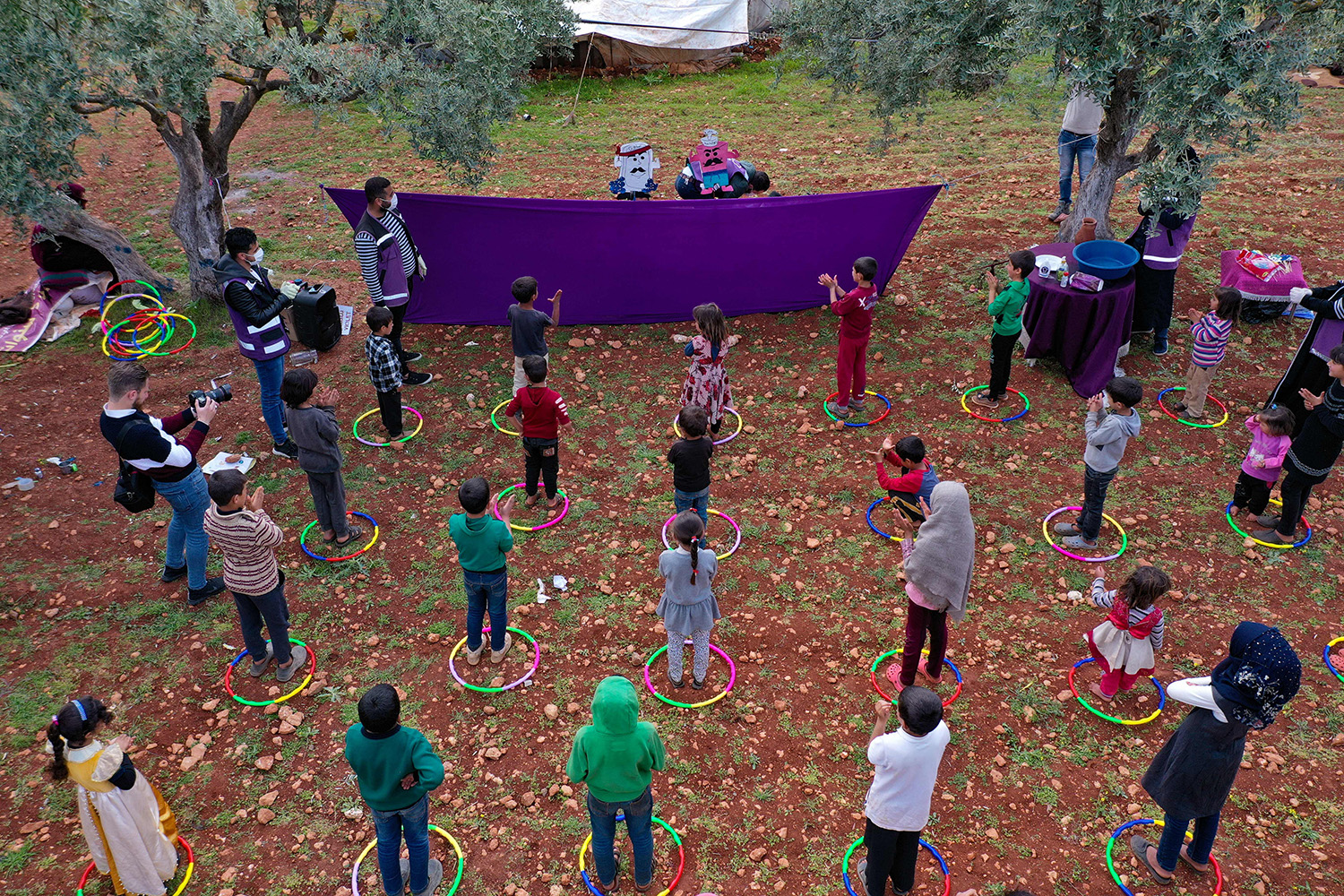 Volunteers perform a puppet show for children in a camp for displaced Syrians in the village of Kafr Yahmul, Syria, on April 7. The purpose of the show was to teach children about the coronavirus and the methods used to limit its spread. OMAR HAJ KADOUR/AFP via Getty Images