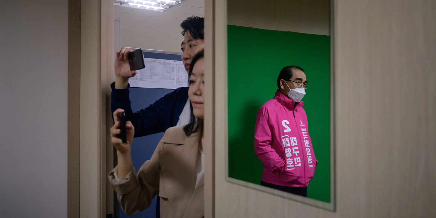 An aide records a live video as Thae, seen reflected in a mirror, speaks at his campaign headquarters in the Gangnam district of Seoul on March 28.
