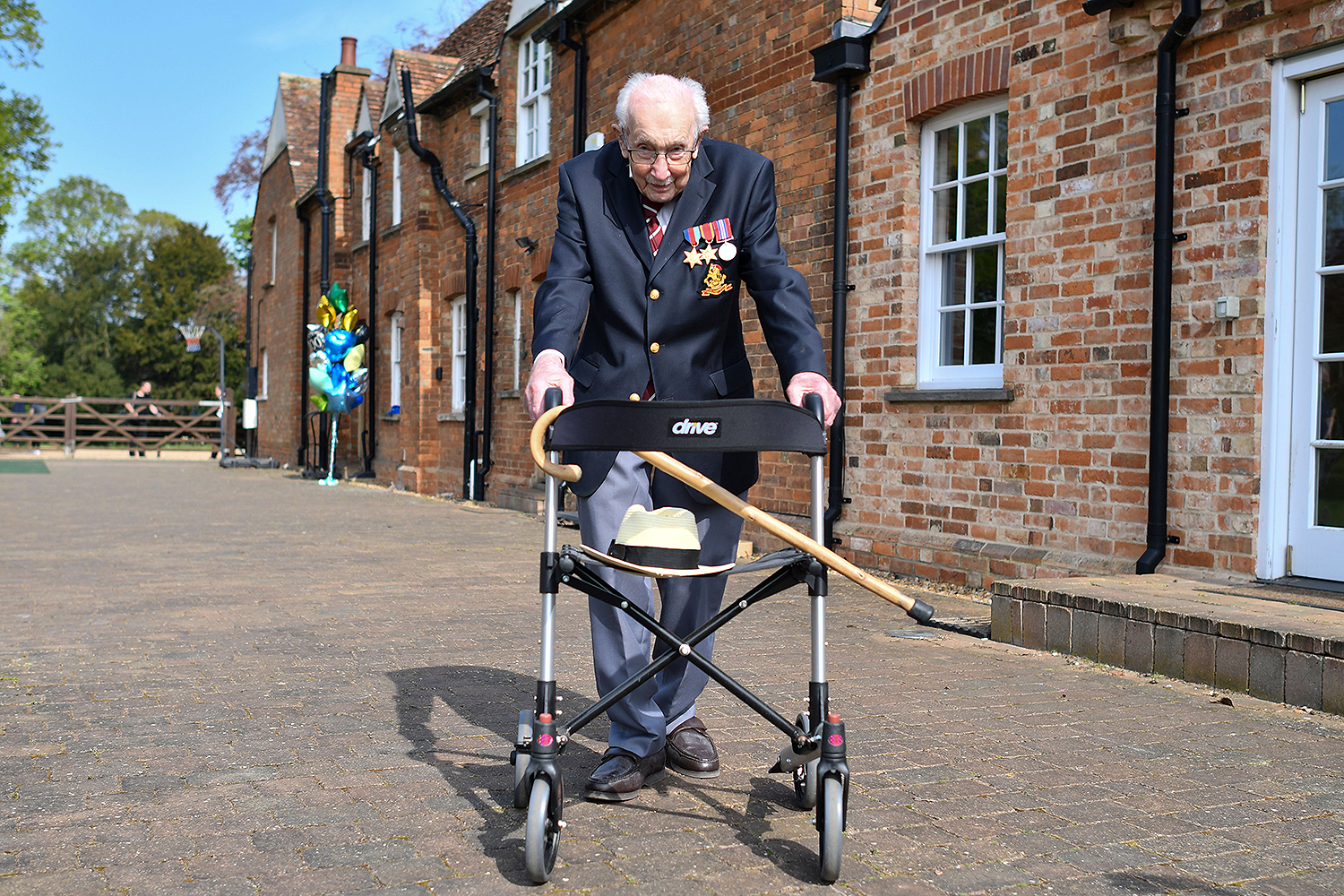 British World War II veteran Capt. Tom Moore, 99, walks a lap of his garden in the village of Marston Moretaine, north of London, on April 16. Moore walked 100 laps to raise money for the U.K.'s National Health Service. JUSTIN TALLIS/AFP via Getty Images