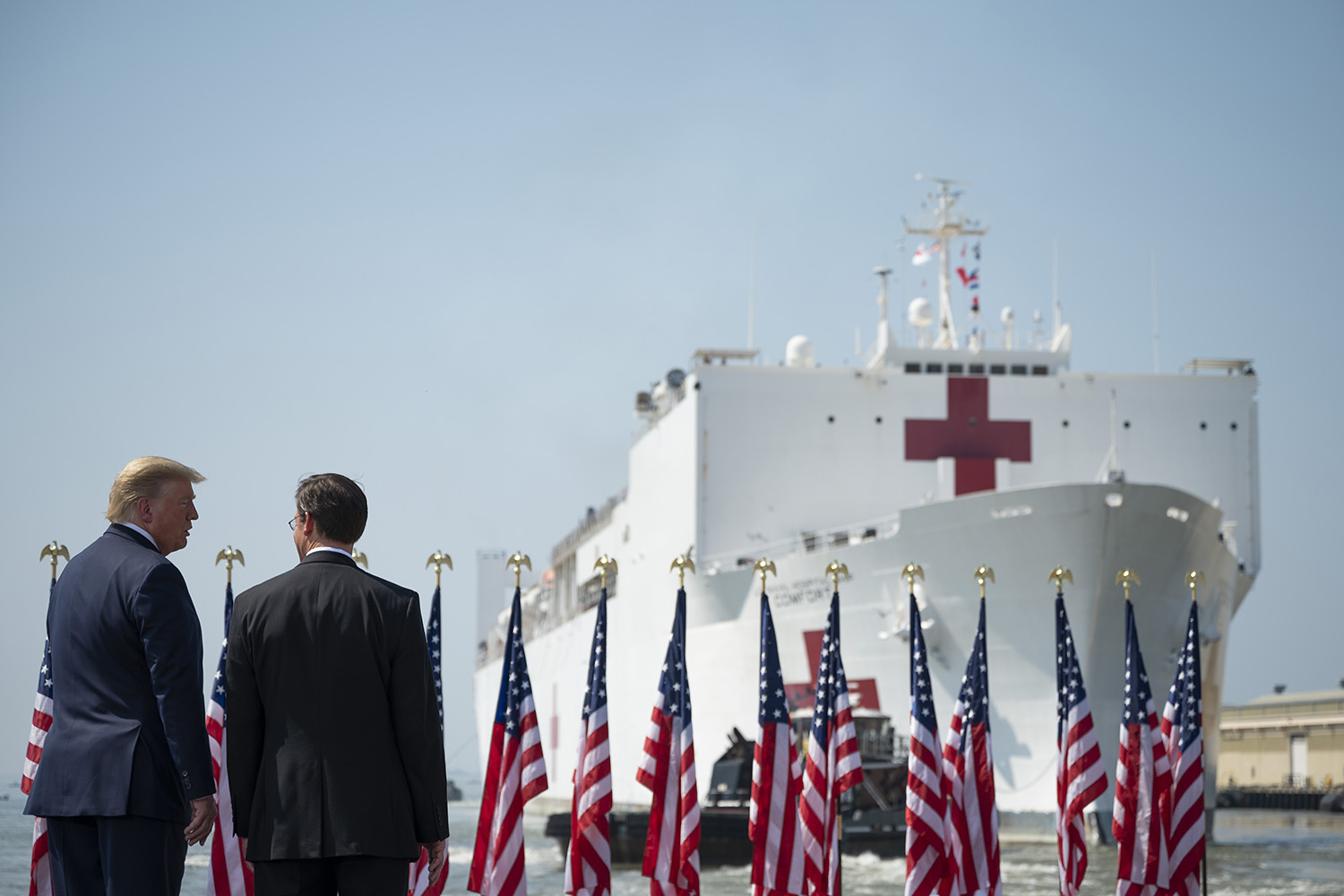 U.S. Defense Secretary Mark Esper (right) and President Donald Trump watch as the U.S. Navy hospital ship Comfort departs Naval Base Norfolk in Virginia on March 28. The Comfort was sailing to New York City to aid in the coronavirus outbreak. JIM WATSON/AFP via Getty Images