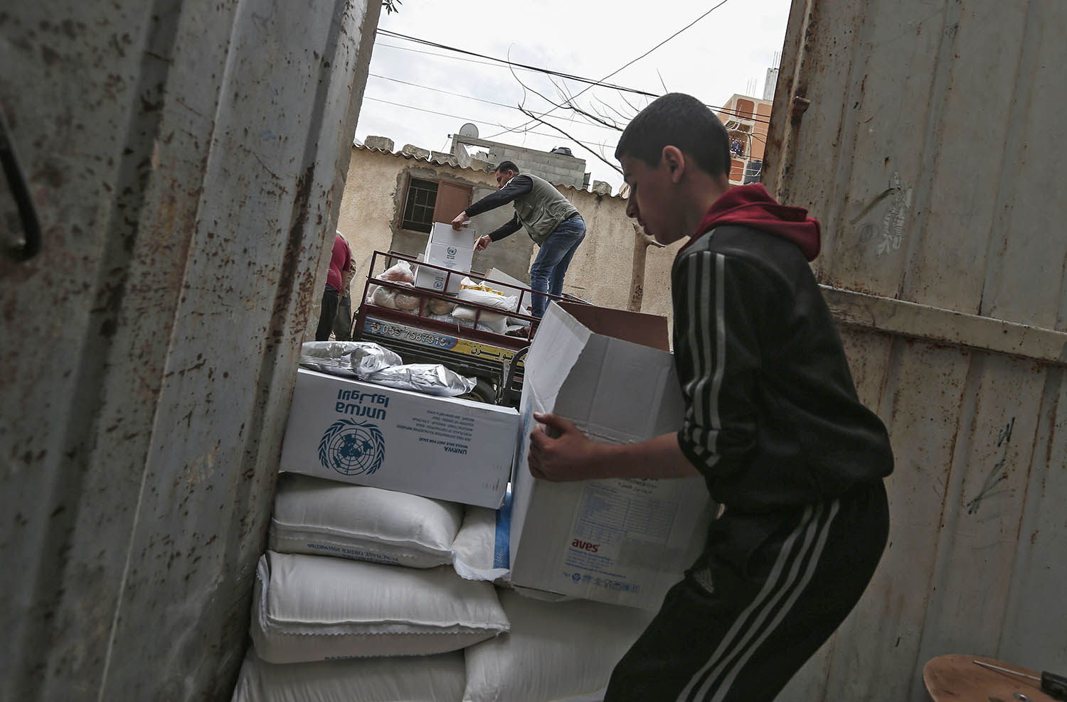 A Palestinian youth transports food rations stacked at his family home doorway by workers with the U.N. Relief and Works Agency for Palestinian Refugees in Gaza City on March 31, 2020, as aid is delivered rather than distributed at a U.N. center, due to the COVID-19 pandemic.