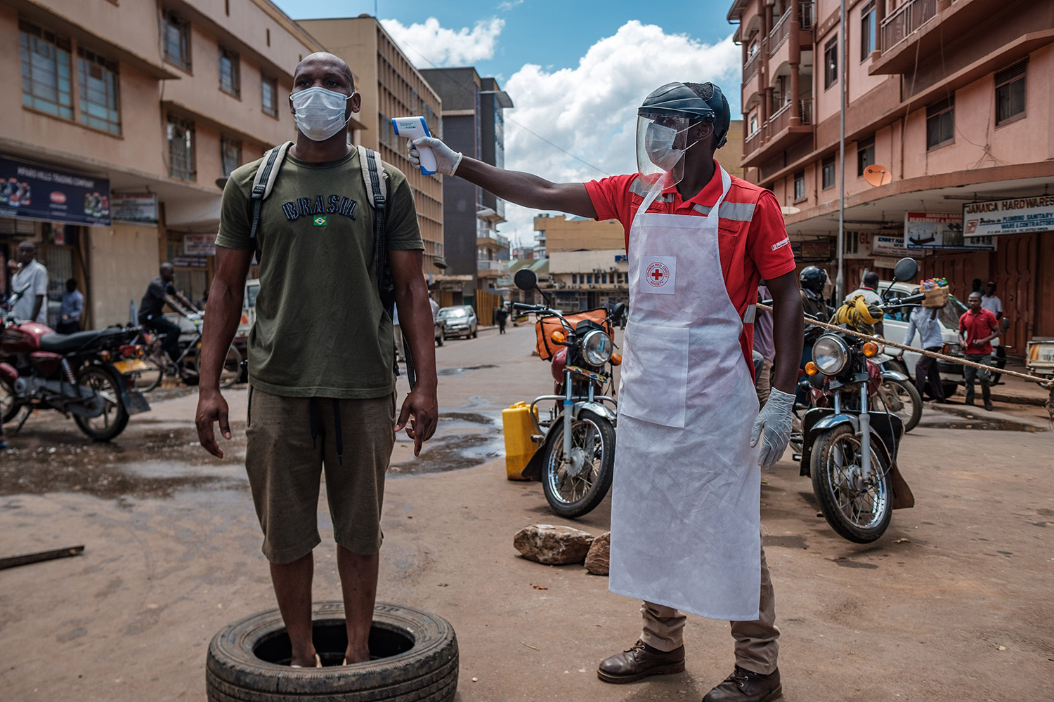 A Red Cross volunteer measures the temperature of a man before he is allowed to enter the Nakasero Market in Kampala, Uganda, on April 1. SUMY SADURNI/AFP via Getty Images