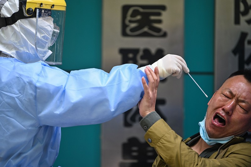 A man being tested for COVID-19 reacts as a medical worker takes a swab sample in Wuhan, China, on April 16. HECTOR RETAMAL/AFP via Getty Images