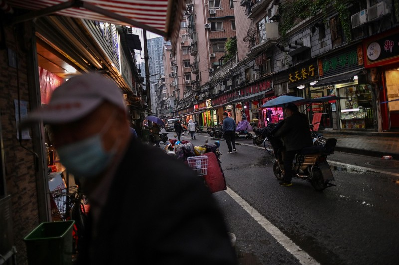 A man, wearing a face mask as a preventive measure against the spread of the novel coronavirus, walks past food stalls in a neighborhood in Wuhan, China's central Hubei province, on April 20.