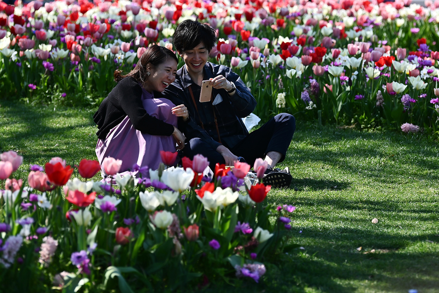 A man and woman chat amid tulips in Yamashita Park in Yokohama, Japan, on April 4. CHARLY TRIBALLEAU/AFP via Getty Images