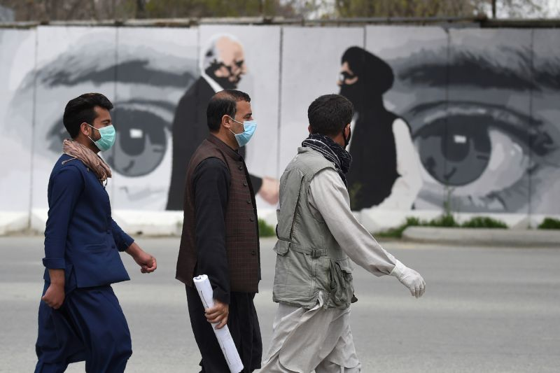 Men wearing face masks walk past a wall painted with images of U.S. Special Representative for Afghanistan Zalmay Khalilzad and Taliban co-founder Mullah Abdul Ghani Baradar in Kabul on April 5.