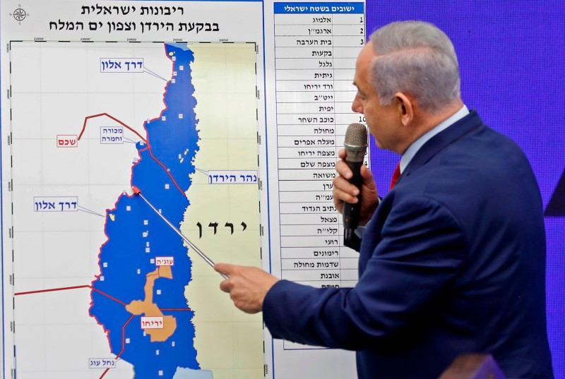 Israeli Prime Minister Benjamin Netanyahu points at a map of the Jordan Valley.