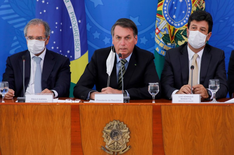Brazilian President Jair Bolsonaro (C) talks next to Brazilian Minister of Economy, Paulo Guedes (L) and Brazilian Minister of Health Henrique Mandetta (R) during a press conference regarding the coronavirus pandemic in Brasilia on March 18, 2020.