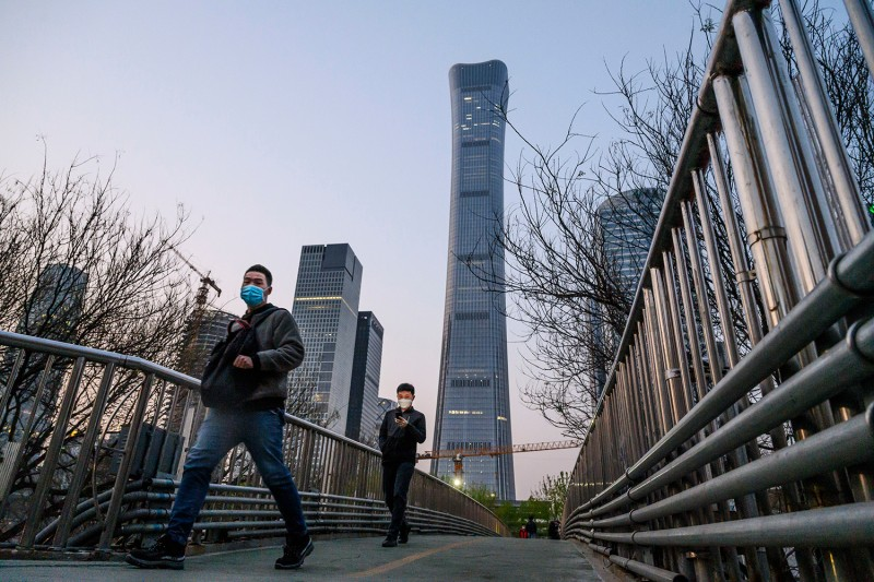 Chinese commuters wear protective masks during rush hour in Beijing's central business district on April 7.