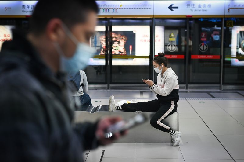 Commuters look at their cell phones in a subway station in Beijing on April 11 amid the coronavirus pandemic.