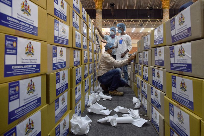 Volunteers apply stickers to boxes of emergency supplies to be distributed to people in need during the coronavirus pandemic in Bengaluru, India, on April 6.