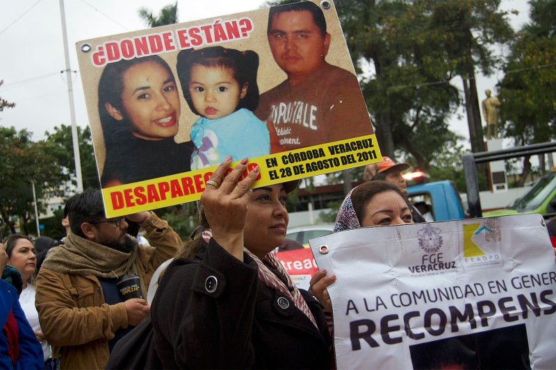 Alma Rosa Preciado marches with a photo of her disappeared daughter and granddaughter in Poza Rica, Veracruz, on Feb. 21.