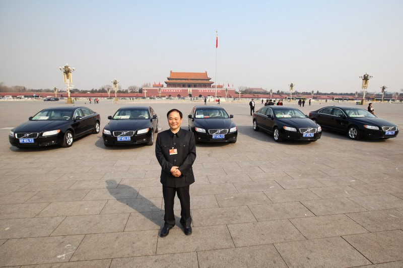 Li Shufu, the chairman of China's Zhejiang Geely Holding Group, poses for photographs in front of Volvo cars in Tiananmen Square during the opening session of the National People's Congress in Beijing on March 5, 2011.