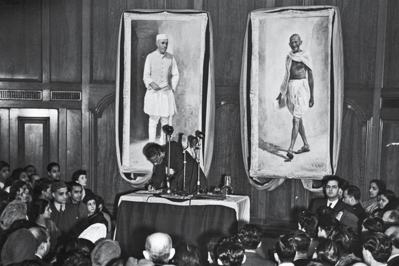 India's high commissioner in London, V.K. Krishna Menon, signs the oath of allegiance to the Indian Constitution at India House in London in front of paintings of Jawaharlal Nehru and Mohandas Gandhi on Jan. 26, 1950.