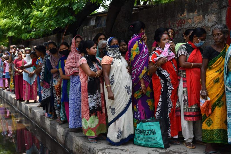 People in need stand in queue as volunteers distribute free food packets in Guwahati, India, during a government-imposed nationwide lockdown against the spread of the coronavirus.